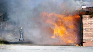 Palomiehet sammuttavat liekehtivää rivitaloa.