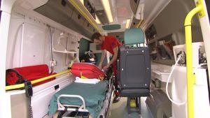 Ensihoitaja tarkastaa varusteita ambulanssissa.
