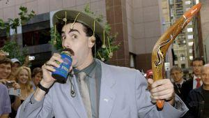 Borat juo olutta bumerangi kädessä