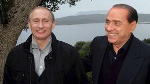 Venäjän pääministeri Vladimir Putin ja Italian pääministeri Silvio Berlusconi hymyilevät vierekkän. Taustalla Italian järvimaisemaa.