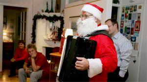 Joulupukki soittaa haitaria perheelle jouluaattona.