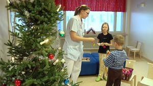 Lastenosaston hoitaja Kaisa Ronkanen koristelee joulukuusta lasten kanssa.