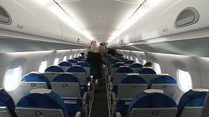 Matkustajia ja lentoemäntä Finnairin lentokoneen matkustamon käytävällä.