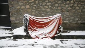 Punaisesta ja vihreästä muovipressusta koottu hätämaja nukkumista varten pariisilaisen kadun jalkakäytävällä. Sen päälle on satanut lunta.