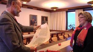 Kansliapäälliikkö Jouko K. Lehmusto vastaanotti lietolaisen Merja Koivuniemen tekemän kopiopergamentin joulurauhanjulistuksesta.