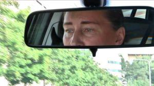 Naisen kasvot auton taustapeilissä.