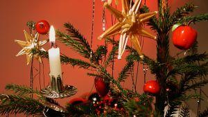 Koristeltu joulukuusi, jossa palavia kynttilöitä