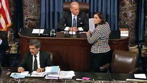 Yhdysvaltain senaatin puhemiestä jututtaa mustavalkoiseen jakkuun pukeutunut nainen.
