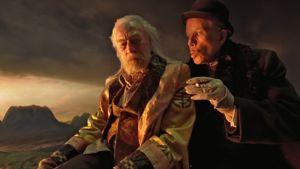 Knallihattuinen ja ohutviiksinen keikari juttelee vanhalle miehelle. Taustalla aurinko vaipuu tummien pilvien vaippaan.