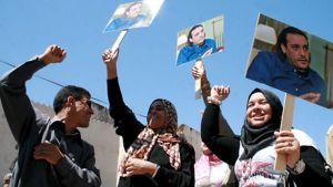 Mies ja kaksi naista heiluttavat kylttejä, jossa on Hannibal Gaddafin kuva.