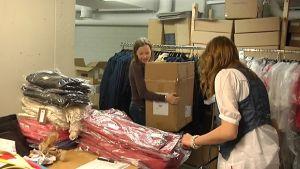 Kaksi opiskelijaa vaatetusliikeen varastotöissä.