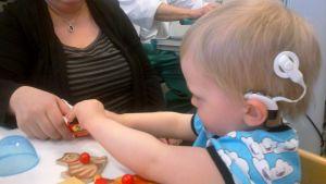 Pieni poika leikkii pöydän ääressä