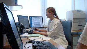 Nainen käyttää tietokonetta lääkärin vastaanotolla.