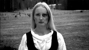 Kuvakaappaus elokuvasta,kansallispukuinen nainen, jonka kasvoissa mustelmia.