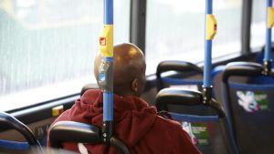 Tummaihoinen mies istuu bussin penkillä.