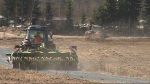 Traktoreita tekemässä peltotöitä