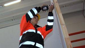 Rakennusalan opiskelija rakentaa harjoitusseinää.