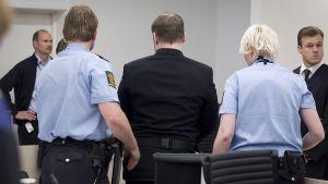 Poliisit saattavat Anders Breivikia ulos oikeussalista.