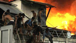 Asukkaat pakenevat Manilan satama-alueella sijaitsevasta palavasta hökkelikylästä.