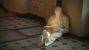 Mies lukee lattialla valkoista kirjaa valkoisissa vaatteissa kasvot hupulla piilotettuna.