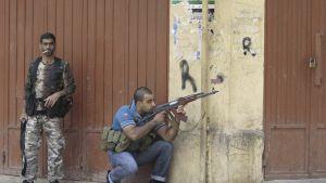 Kaksi aseistettua miestä suojautuu talon kulman takana.