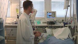 Lääkäri hoitaa potilasta teho-osastolla.