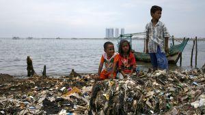 Pojat leikkivät jätteiden täyttämällä tekojärven rannalla.