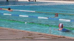 Kolme ihmistä uimassa Porin maauimalan isossa altaassa.