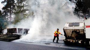 Mies levittää asfalttia tielle.