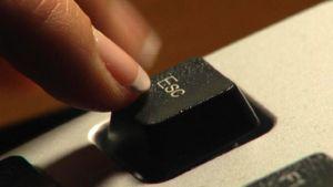 Sormi painaa tietokoneen näppäimistön Esc-painiketta.
