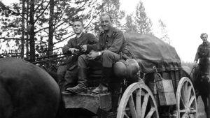 Kaksi saksalaista sotilasta kuormaston hevosrattailla.