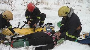 Palomiehet siirtävät naista paareille maastossa
