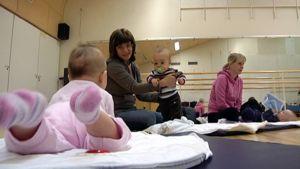 Kaksi pientä vauvaa tutustuvat toisiinsa neuvolan vertaistukiryhmän kokoontumisessa.