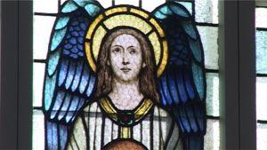 Lasimaalaus kirkon ikkunassa esittää Jeesusta tai enkeliä.