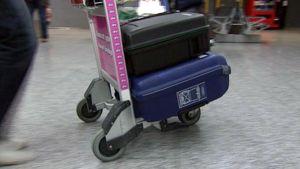 Matkailija matkalaukkuineen lentokentällä