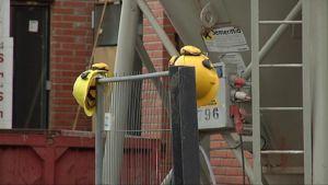 Kaksi kypärää roikkuu aidalla rakennustyömaalla.