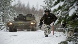 Sotilas juoksee panssarivaunun edessä lumisessa maisemassa.