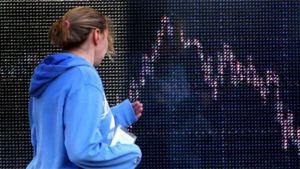 Nainen tarkastelee pörssikäyrää Lontoon pörssissä