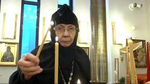 Lintulan luostarin johtaja, igumenia Marina sytyttää tuohuksen kirkossa.
