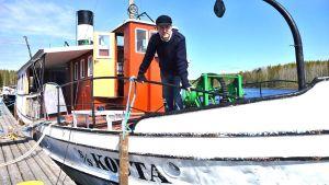 Kouta-laiva on kiinnitettynä laituriin. Olli Leppänen seisoo laivan etukannella.