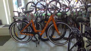 Kuvassa oranssi  sähköpyörä pyöräliikkeessä.