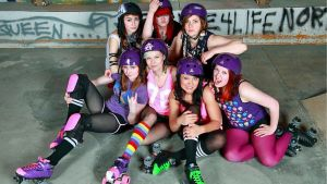 Roller derby naisia istumassa lattialla.