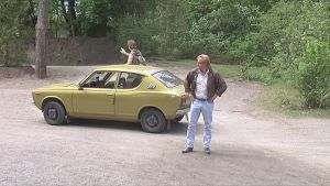 Kaksi miesnäyttelijää ja Datsun 100A -auto Pyynikin kesäteatterissa.