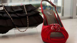 Musta käsilaukku ja punainen kenkä näyteikkunassa
