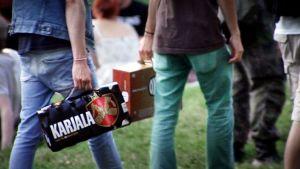 Nuoret kantavat 12-pack olutpakkauksia.