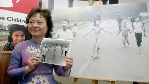 Kim Phuc pitelee kuvaa, jossa hän itse lapsena juoksee alasti pakoon napalmihyökkäystä.