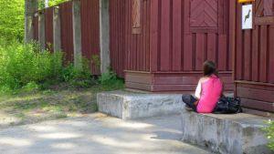 Yksinäinen tyttö istuu selin