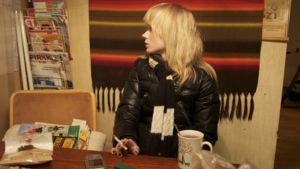 Vaaleahiuksinen tyttö katsoo sivulleen tupakka kädessä ja kahvikuppi edessään.