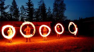 Tulikansa ry:n tuliteatteriesitys pimeässä illassa. Viiden henkilön tekemiä pyöreitä kuvioita hitaalla valotusajalla kuvattuna.
