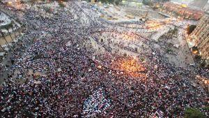Ilmakuva Tahririn aukiosta, jolla on tuhansia mielenosoittajia. Osa rukoilee polvistuneina Mekkaan päin.